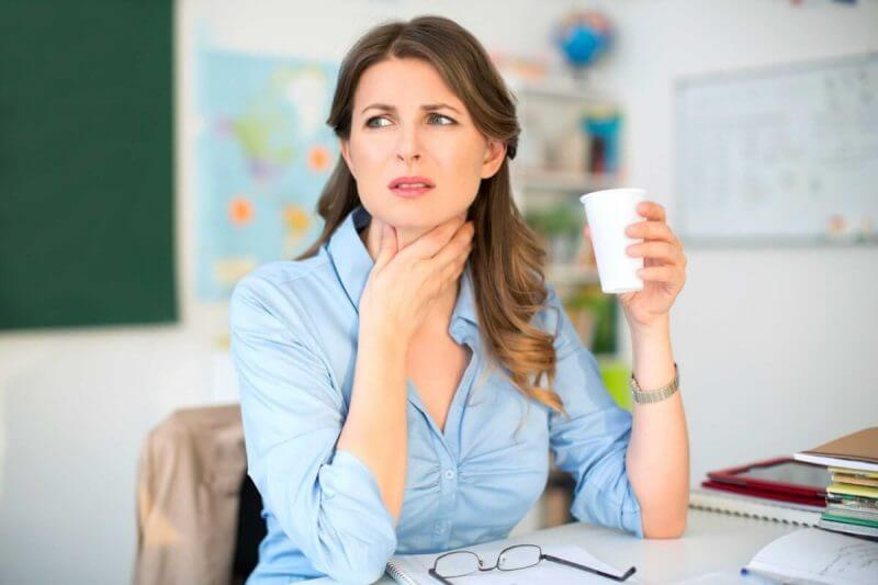 woman holding her neck and a glass on the other side