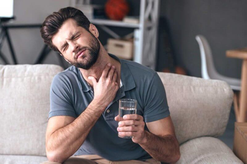 man with acid reflux holding his neck