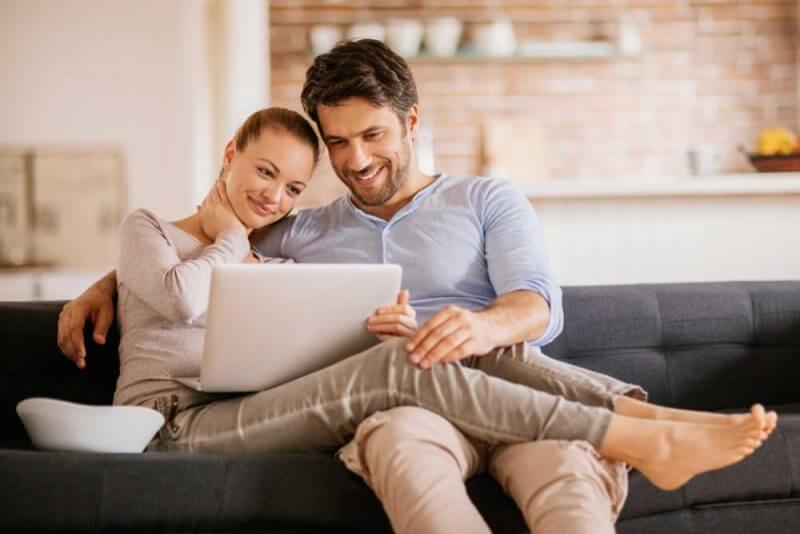 lovers seated together using a laptop