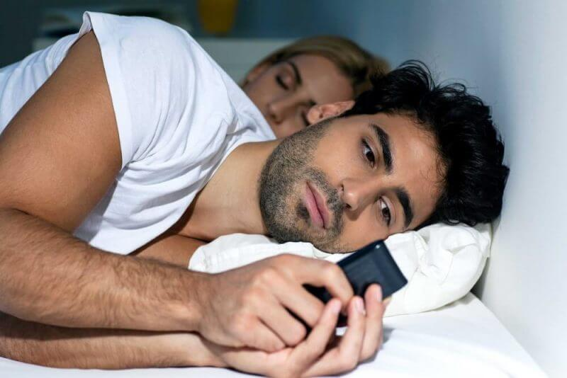 man using a phone secretly in bed