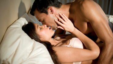 Young lovers in bed kissing.