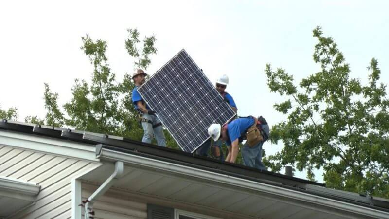 men fixing solar panels