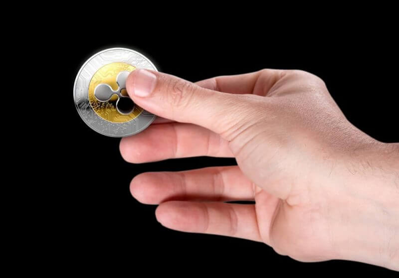 A male hand holding a physical ripple cryptocurrency in gold and silver coin form on a dark studio background