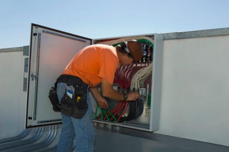 Engineer Working on Electrical Box at Solar Power Plant