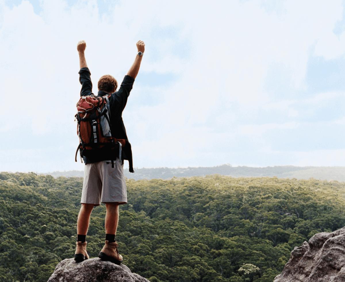 man on a mountain celebrating