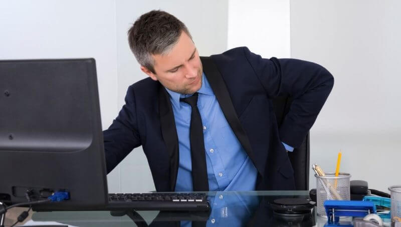 man in office having some back pain