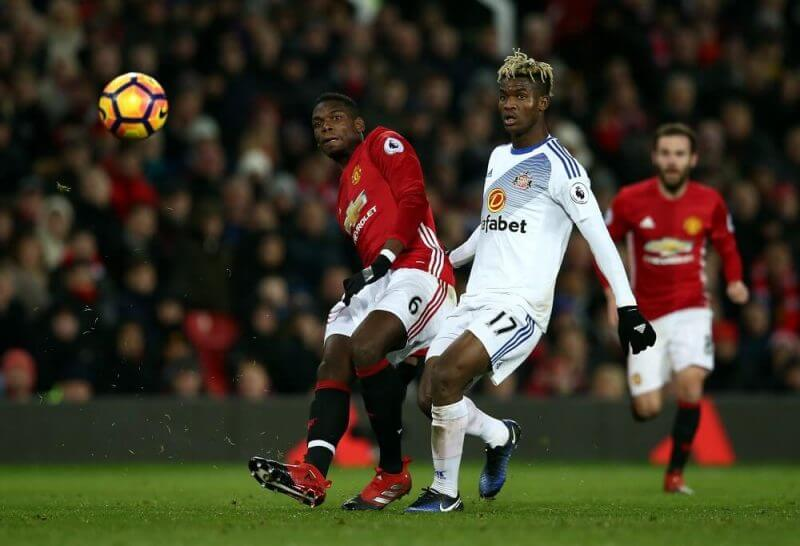 MANCHESTER, ENGLAND - DECEMBER 26: Paul Pogba of Manchester United takes a shot at goal under pressure from Didier Ndong of Sunderland during the Premier League match between Manchester United and Sunderland at Old Trafford on December 26, 2016 in Manchester, England. (Photo by Jan Kruger/Getty Images)