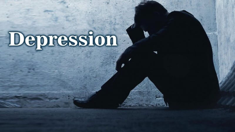 word depression and a man seated on the floor looking stressed
