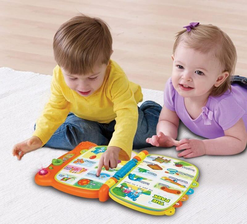 2 toddlers seated working on a book