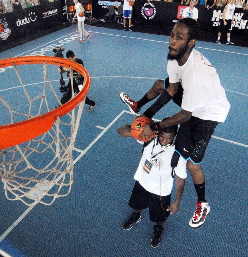 two players playing basketball with one of them jumping high to score