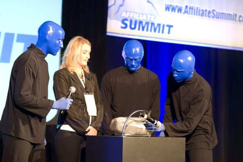 3 people with blue faces and a white woman doing a demonstration