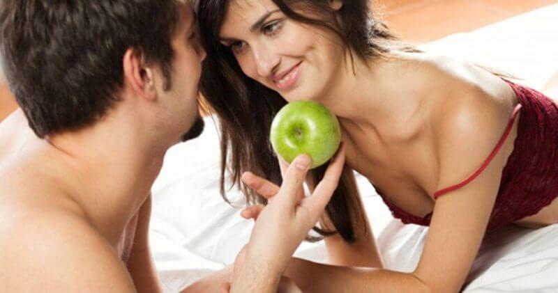 man giving a woman an apple