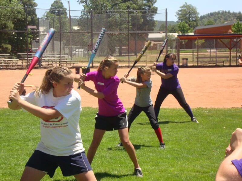 young girls training baseball swing