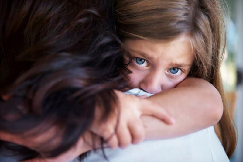 Closeup shot of a crying little girl hugging her mom around her neck