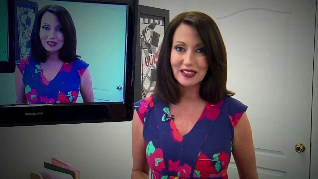 a lady smiling and a screen on the background with her image