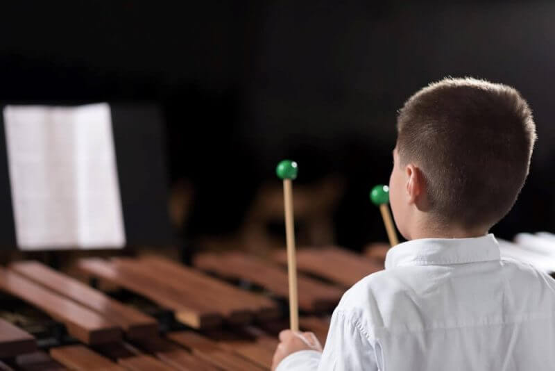 portrait of a young man learning to play the xylophone