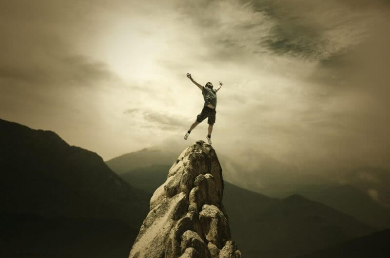 person standing on a cliff and celebrating