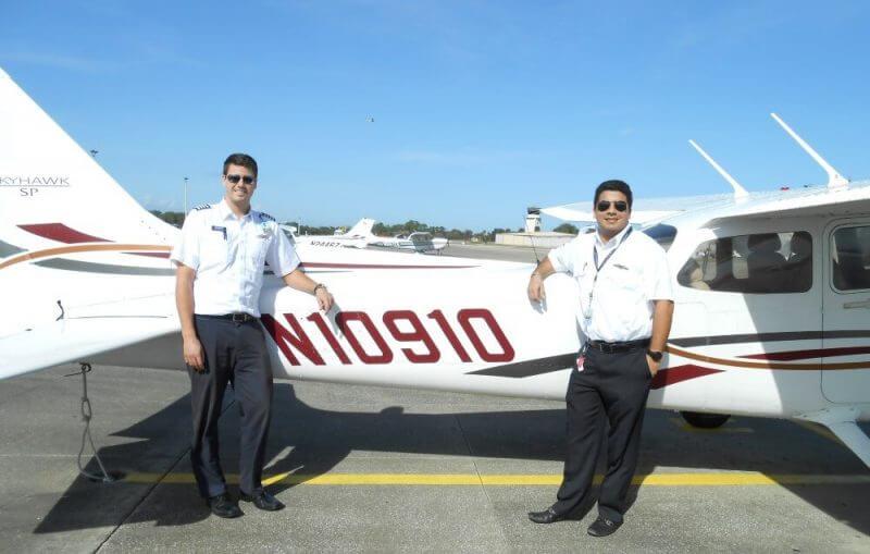 two pilots beside a plane