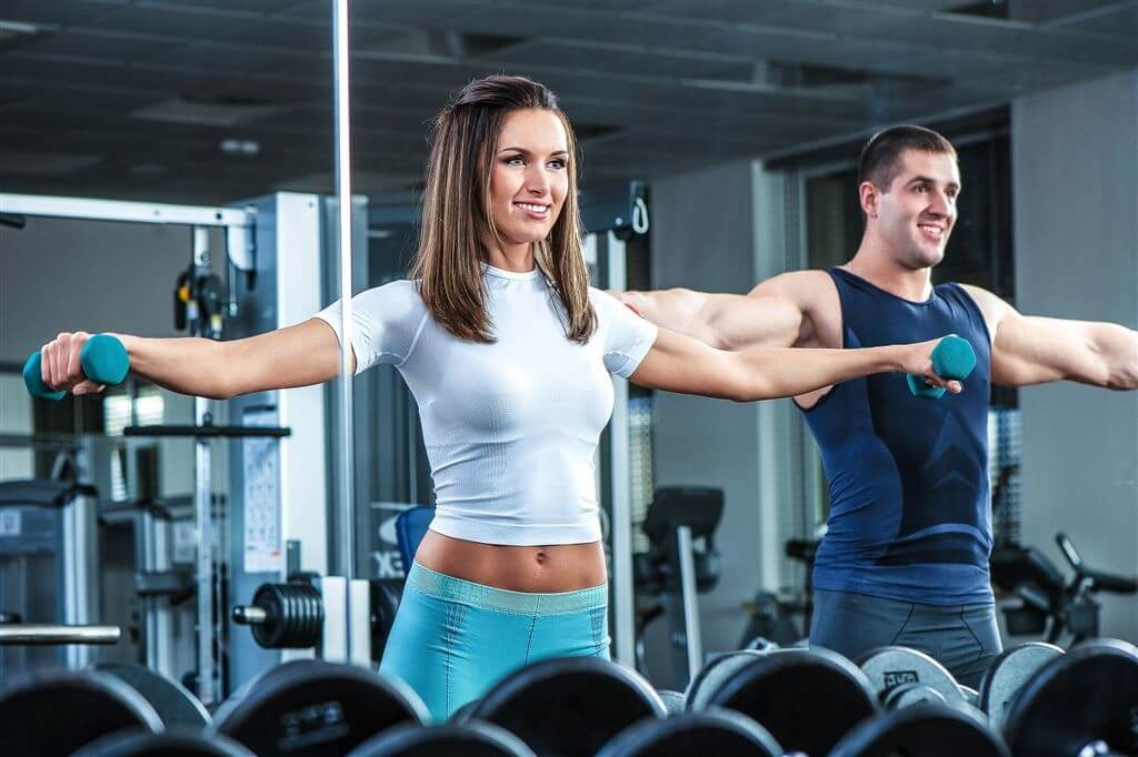 a man and woman lifting weights in a gym