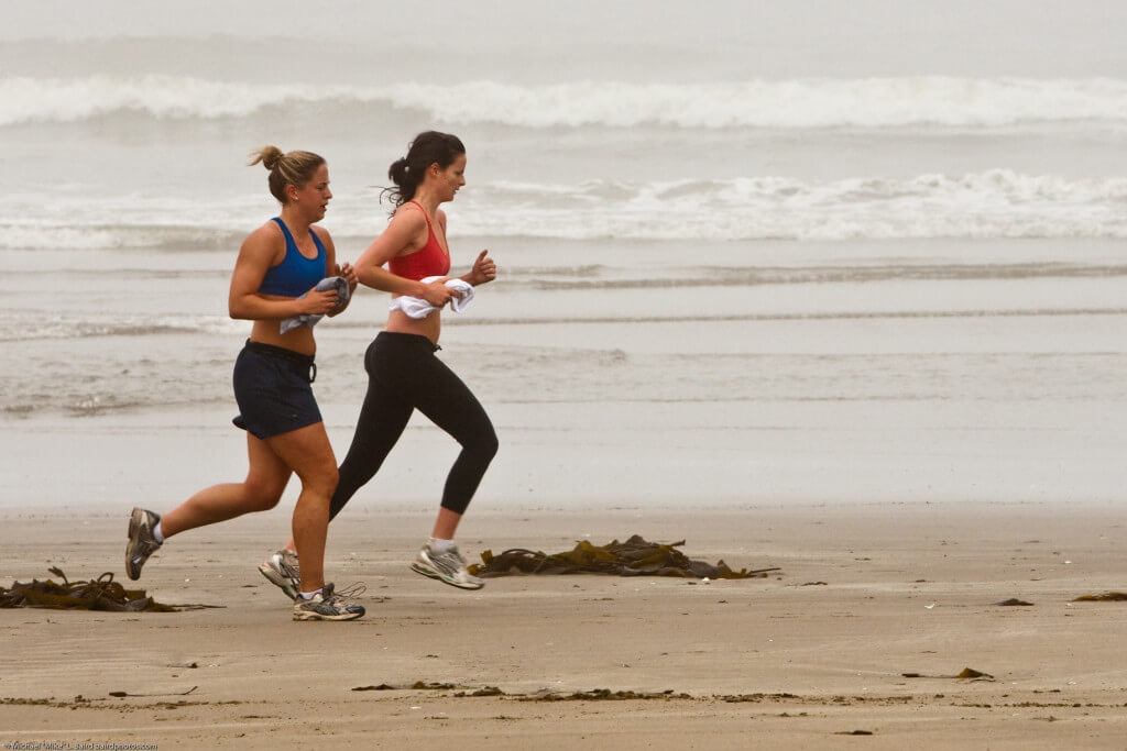 "Two female joggers on foggy Morro Strand State Beach, seen during a Digital Photo Walk http://photomorrobay.com/walks/ led by Mike Baird, 17 May 2009. Eighteen participants enhanced their basic camera and photography skills on this foggy morning outing. Photo by Michael ""Mike"" L. Baird, mike [at} mikebaird d o t com, flickr.bairdphotos.com; Canon 1D Mark III, 70-200mm f/2.8 IS, handheld, circular polarizer."