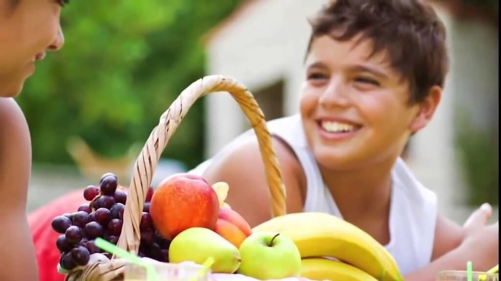a basket of fruits and two people smiling at each other
