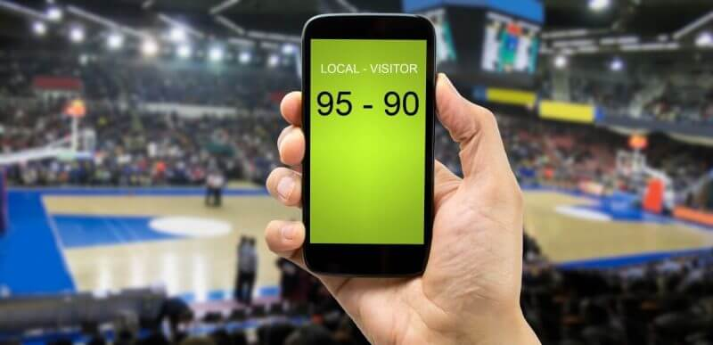 betting man through his smart phone in a basketball arena