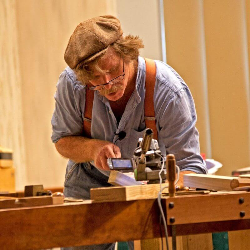 a man keenly working on a piece of wood