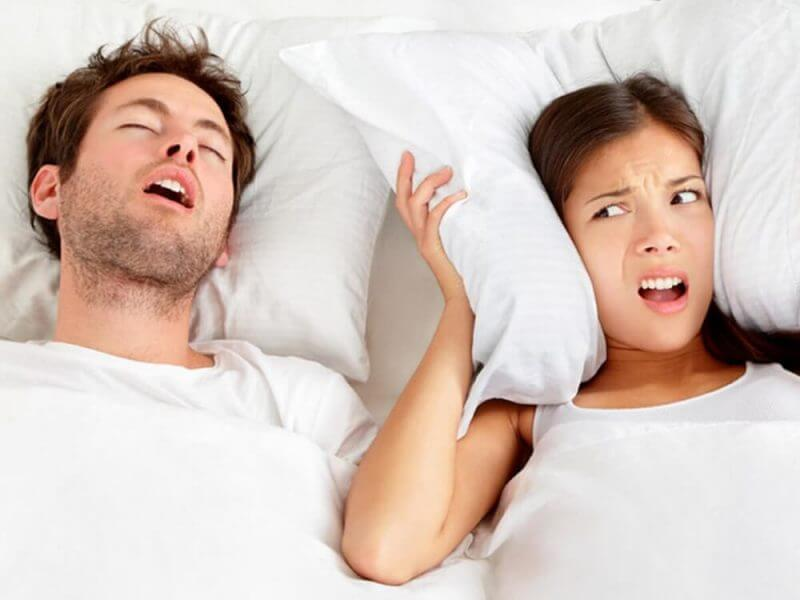 man snoring and woman next to him closing her ears