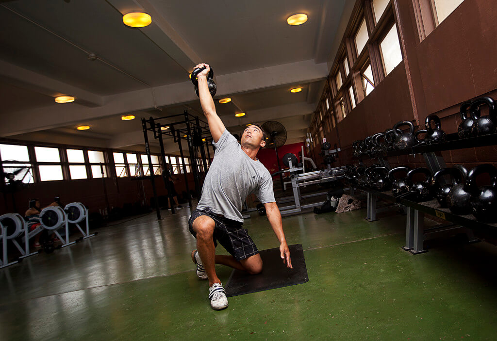 Navy Lieutenant Cmdr. Andy Silvestri, a dentist with 21st Dental Company and 35-year-old from San Jose, Calif., performs Turkish get-ups during a circuit workout at the High Intensity Tactical Training (HITT) Center on Marine Corps Base Hawaii, Aug. 14, 2012. Open since August 2011, the HITT Center is a gym devoted to supporting circuit and high-intensity cross training. Equipment featured inside includes battle ropes, BOSU and Dyna balls, ellipticals, kettle bells, medicine balls, plyometric boxes, rowing machines and TRX suspension training rings. The center, located in Building 1034 next to the 3rd Marine Regiment Satellite Fitness Center, is available for use by service members Monday through Friday, from 6 a.m. to 9 p.m.