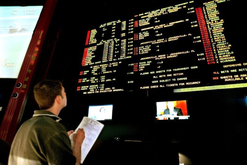 Steve Borys, an admin operator at Caesars Palace, checks the 2006 NCAA men's college basketball tournament bidding sheets to make sure the numbers match the board at the Caesars Palace sports book in Las Vegas, Monday, March 13, 2006. (AP Photo/Jane Kalinowsky)