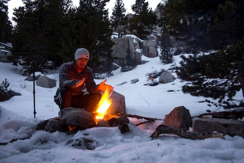 man recing warmth from a camp fire