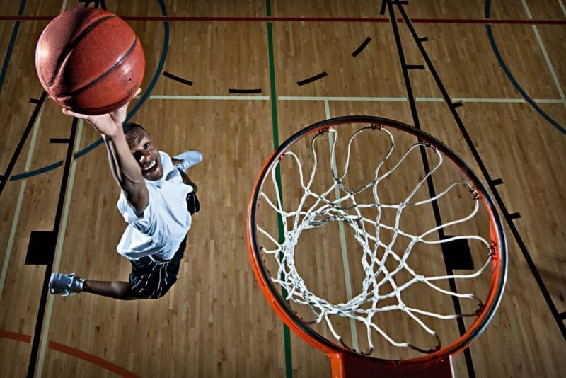 A young man dunking a basketball. Focus on the basketball.