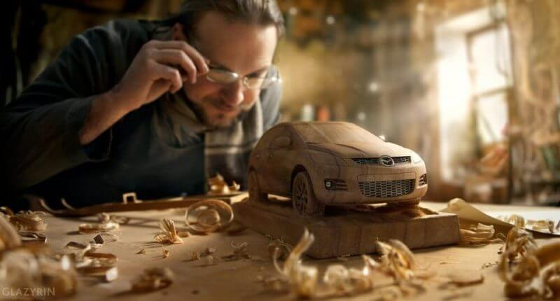 a man closely inspecting a wood model car