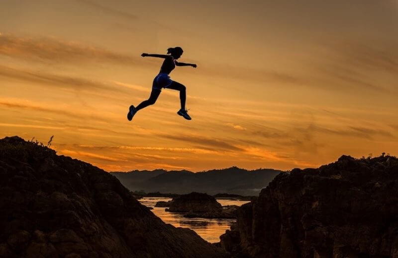 woman jumping a cliff