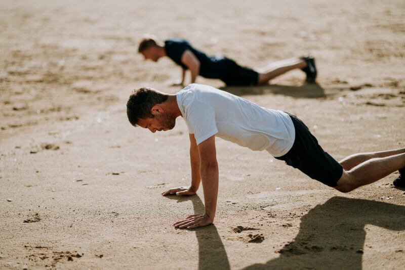 Two man working out in the sand near the beach.