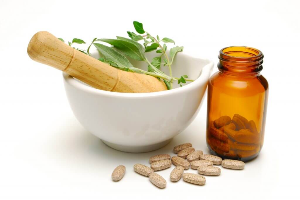 medicinal herbs and tablets on white background