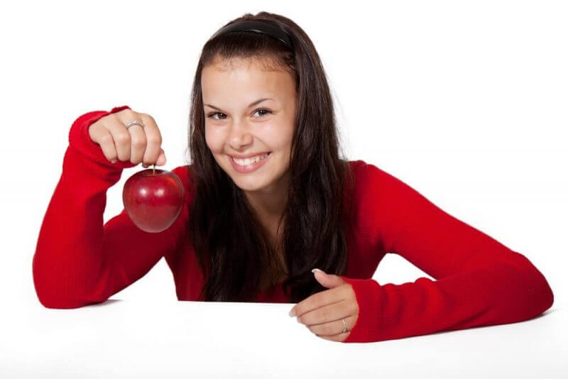 a beautiful woman in red and holding an apple