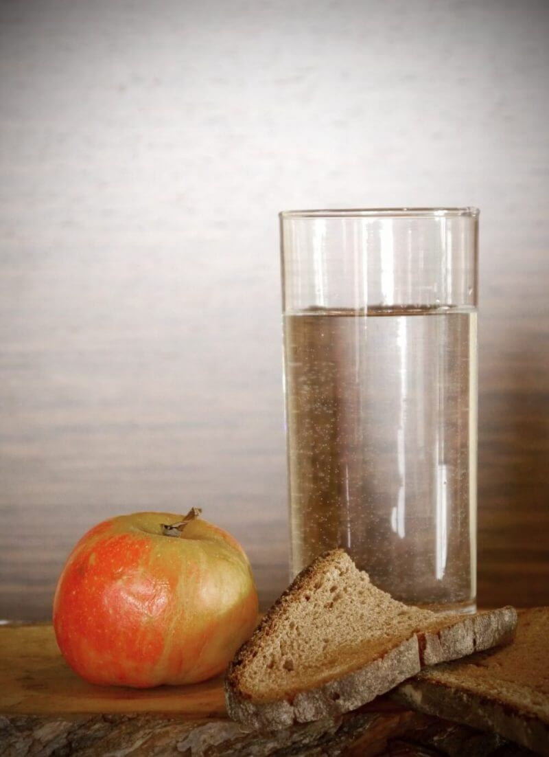 a glass full of water , apple and a slice of bread
