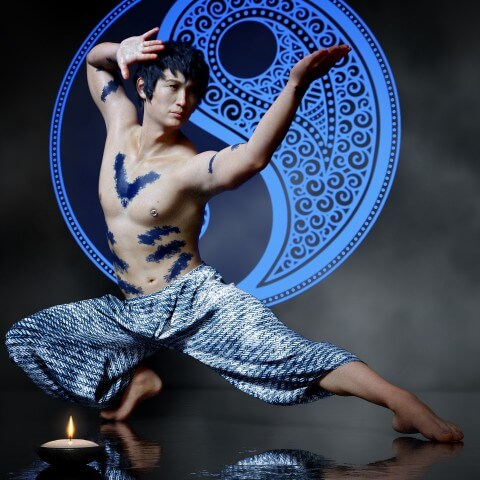 a young martial artists in a fight mode position wearing blue kung fu pants and topless