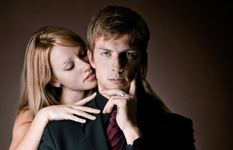 a woman romantically touching a man's neck