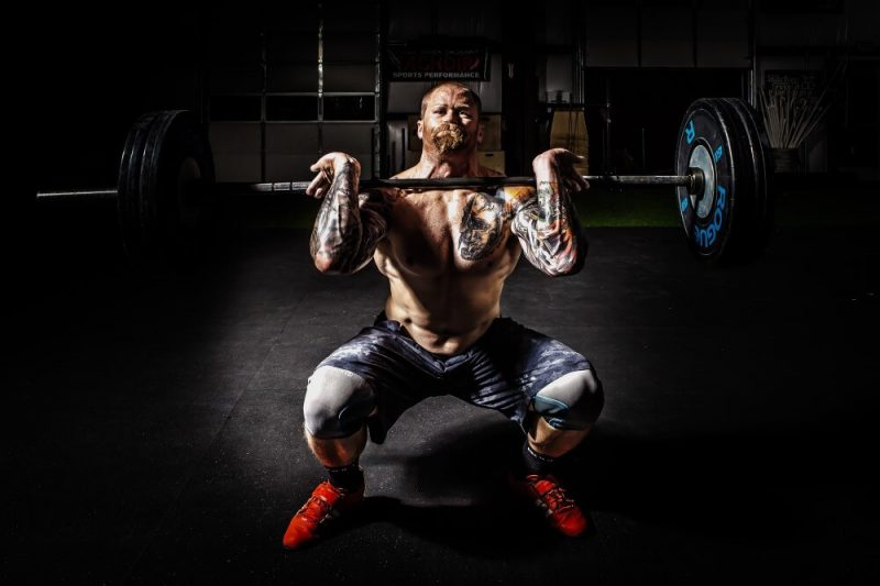 musculine man lifting heavy weights