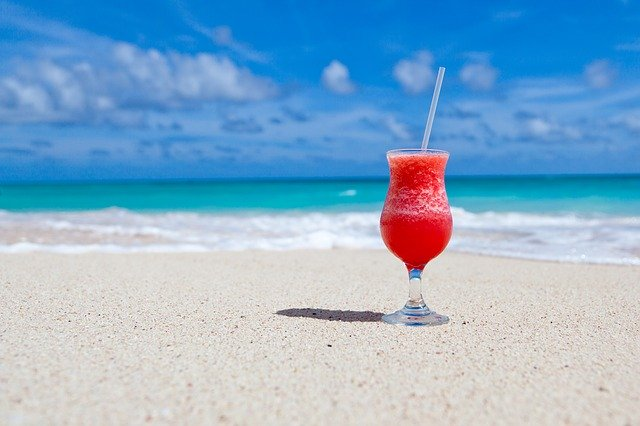 TutorJobsOnline.com freedom represented by a red drink on sand and a beach view from behind