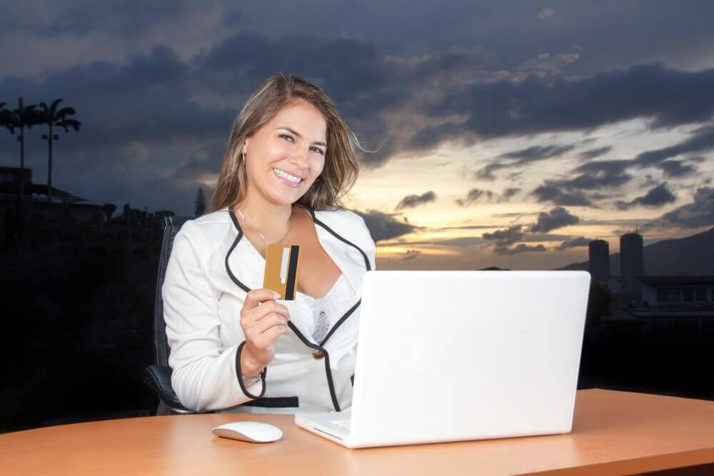 working woman in white holding a credit card and working on her laptop