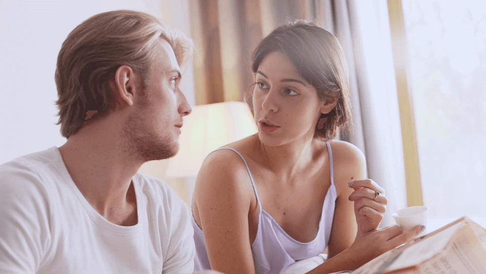 beautiful-caucasian-pair-sitting-at-bed-talking-with-each-other-smiling-laughing-reading-magazine-in-morning-in-slowmotion_h6gusfekl_thumbnail-full01