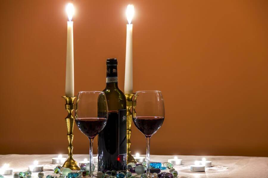 wine, two wine glasses and candles on the table