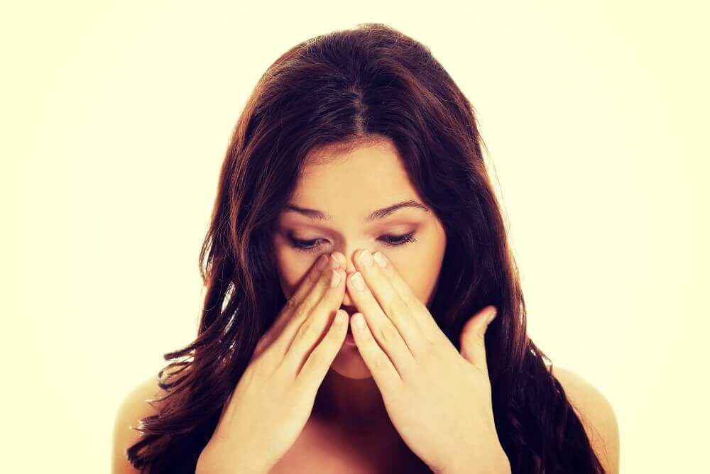 Young woman suffering from sinus pressure pain.