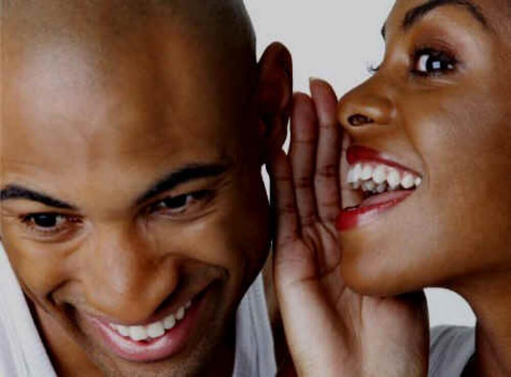 black woman whispering to a man