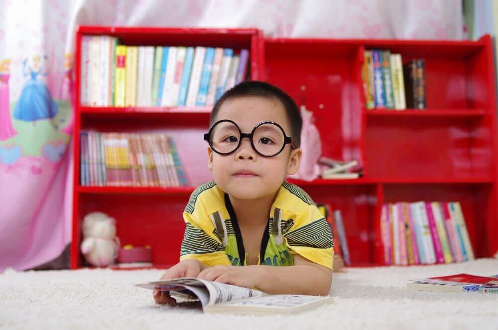 a baby with glasses reading