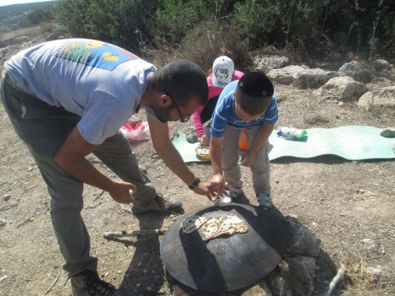 father and son out camping trying to roast food