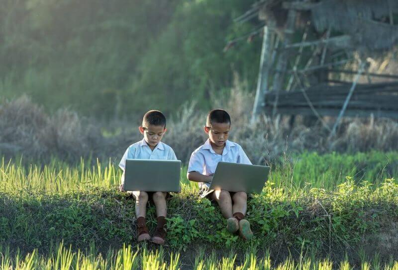 two kids using laptops